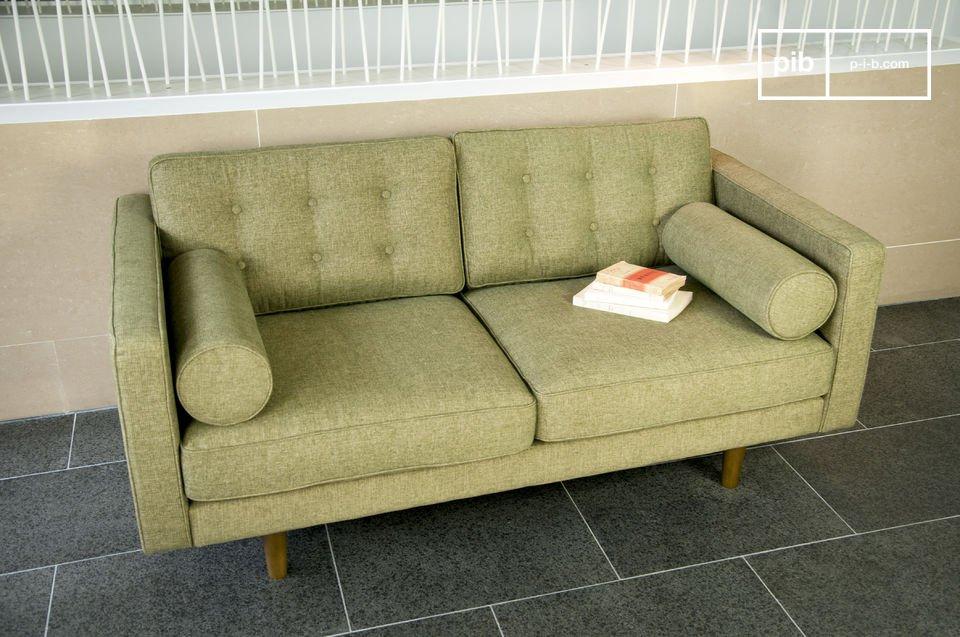 Questo divano ha un look che ricorda gli anni 50, con i braccioli cilindrici e le gambe a compasso
