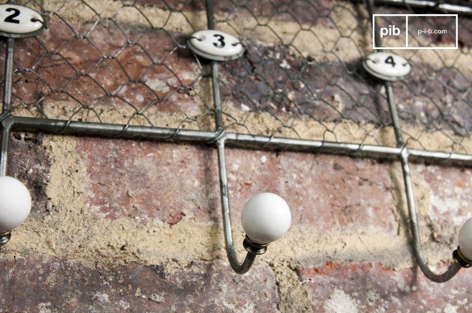 Questo appendiabiti in metallo è pratico, con i suoi cinque ganci numerati e la mensola robusta
