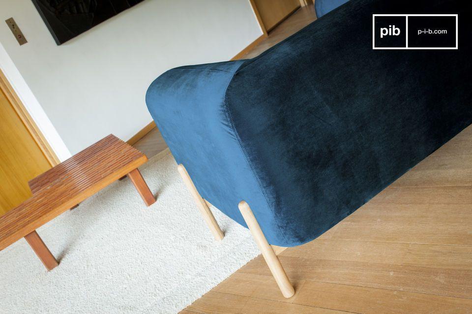 Le generose forme della poltrona Viela sono accompagnate da un rivestimento in velluto blu