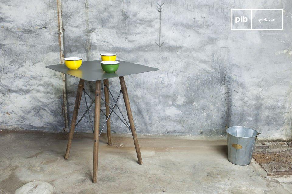 Quattro sottili barre di metallo uniscono la superficie metallica con le gambe in legno