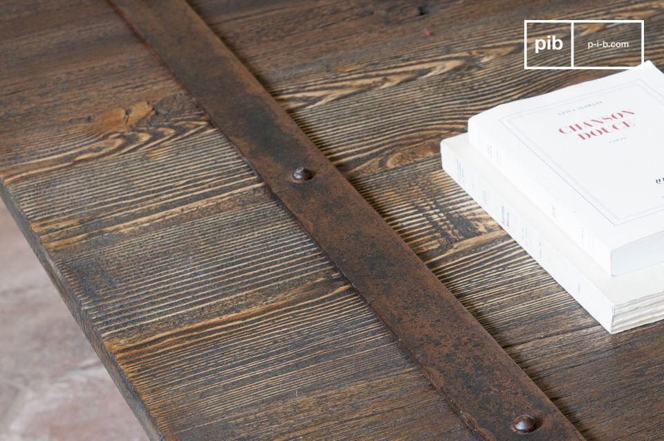 Le bande metalliche che circondano il piano di legno del tavolo sono state fissate con delle viti