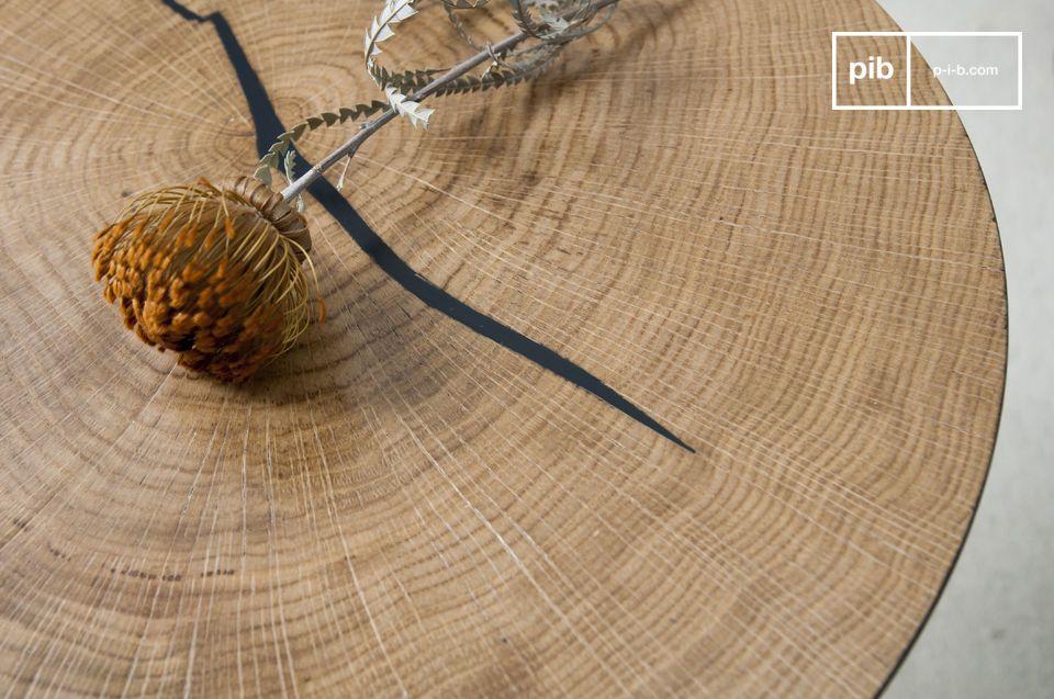 La fessura naturale della sezione in legno è stata riempita di nero e ci ricorda il colore della