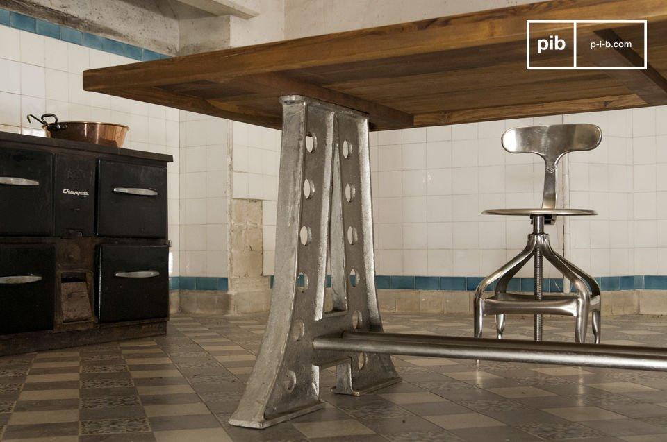 Le gambe di acciaio in stile Torre Eiffel e il piano di spesso teak rendono questo tavolo molto